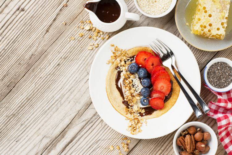 Healthy breakfast trend. Fine grain oat pancakes with chocolate cream and assorted fruits and berries strawberries, blueberries, chia seeds, granola, nuts and honey. The concept of organic healthy food super power. selective focus